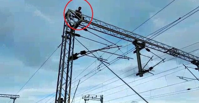 High drama at Berhampur railway station as youth climbs atop electric tower High drama at Berhampur railway station as youth climbs atop electric tower